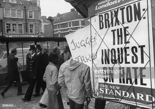 Two policeman in the Brixton Road walk past a news poster which says 'Brixton The Inquest On Hate'