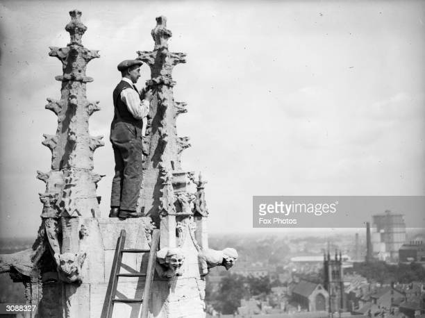 A workman renovating the Gothic spires of the cathedral of St Peter's in York Minster