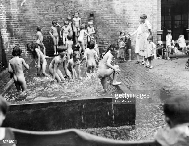 Children at a foundling hospital cool themselves off in a pool during a summer heatwave