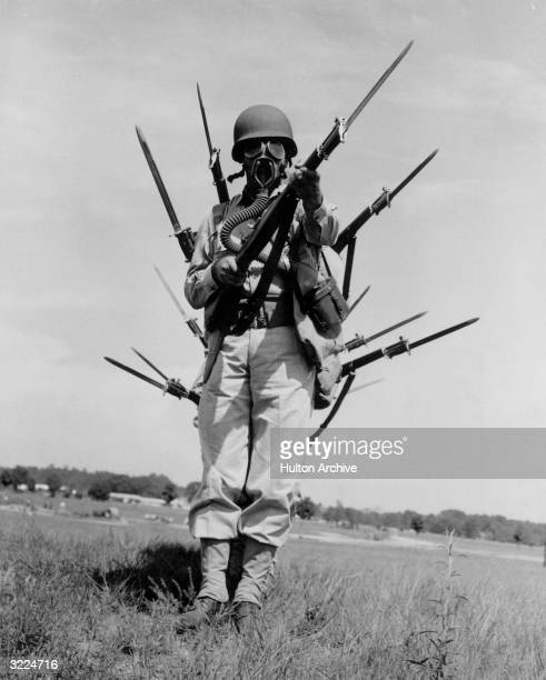 Fulllength view of a US Army soldier wearing a gas mask and holding a rifle with a bayonet as other bayonets protrude from soldiers behind him Fort...
