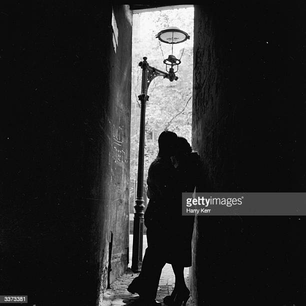 A couple embracing in a narrow darkened alley