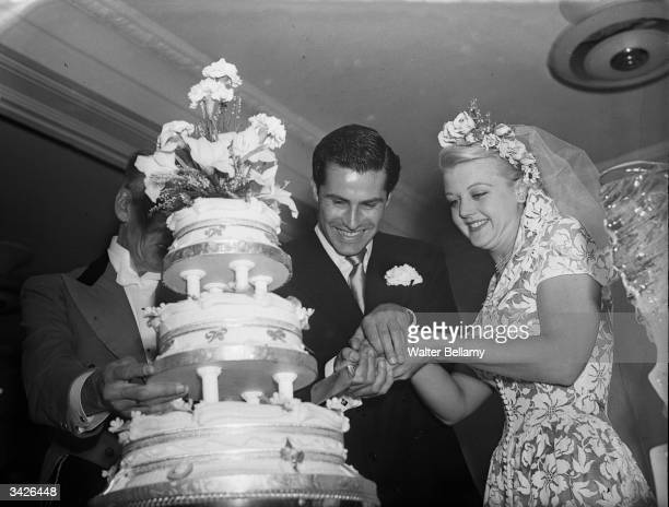 British actress Angela Lansbury and her husband Peter Shaw cutting the cake at their wedding