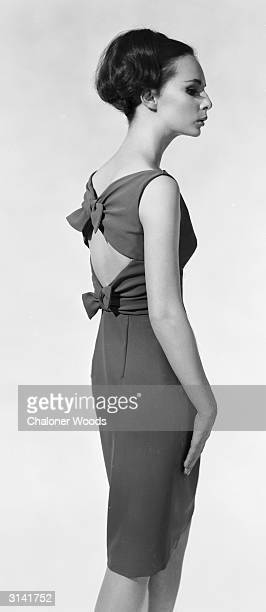A slim fitting sleeveless cocktail dress fastened with two bows at waist and shoulder level over a bare back