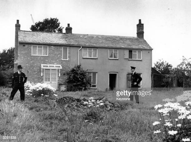 Police stand guard outside Leatherslade Farm at Oakley in Buckinghamshire used as a hideout by the Great Train Robbers