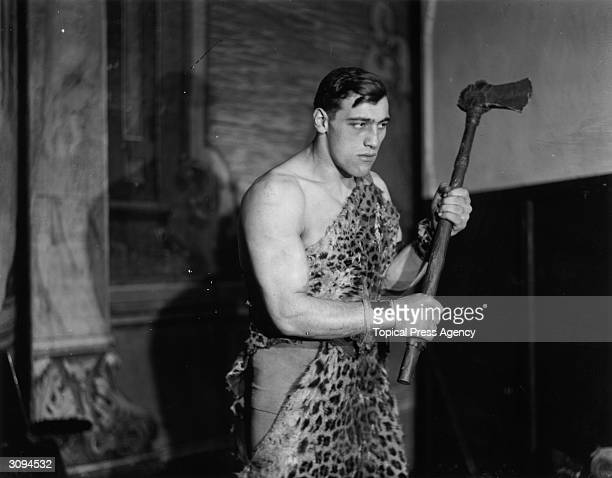 Primo Carnera the Italian heavyweight boxer and wrestler poses in a leopard skin to represent a caveman at a 'Joy of Life' Ball at the Royal Opera...