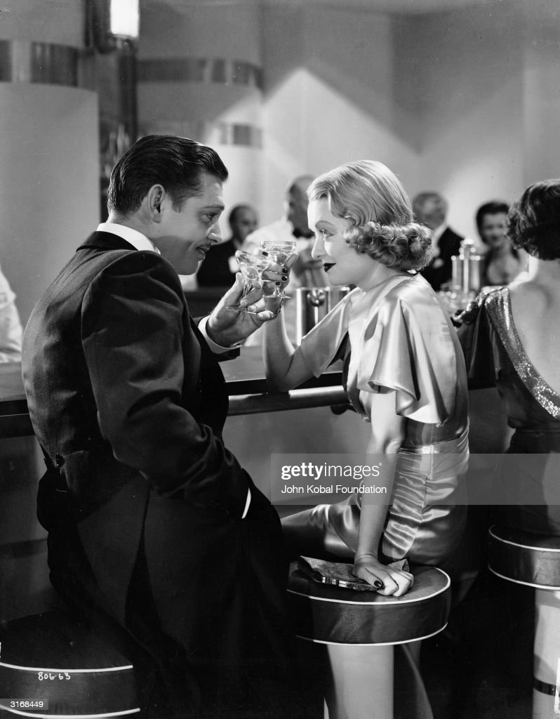 Clark Gable (1901 - 1960) and Constance Bennett (1904 - 1965) raise their glasses in 'After Office Hours', directed by Robert Z Leonard.