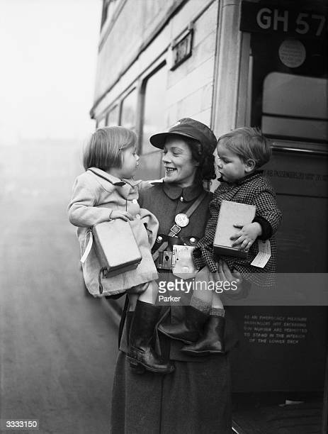 A bus conductress holds two young evacuees who are being taken by bus to a safer part of the country during a London County Council scheme during...