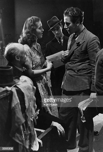 British actress Patricia Roc speaks to British actor and producer Peter Ustinov on the set of the film 'Let the People Sing' To their left is British...