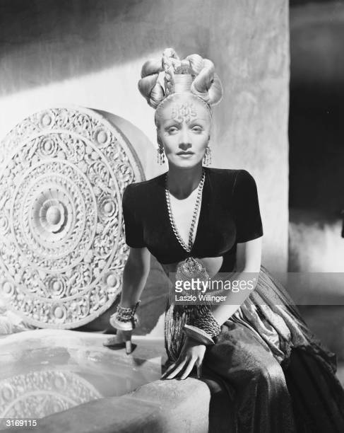 German-born actress Marlene Dietrich poses as the character Jamilla in an oriental costume with an elaborate hairstyle to promote the 1944 film...