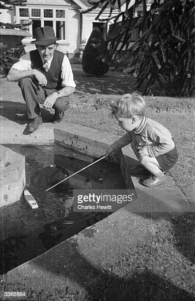 Herbert Chapman who won 20000 on the pools watches his son play with a toy boat in the garden of the house he bought with his winnings Original...
