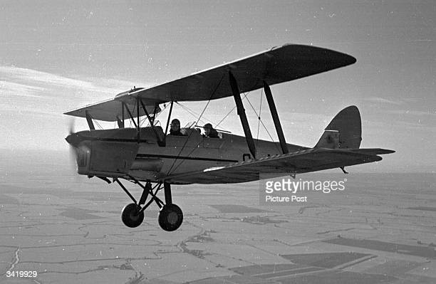 The British actress Valerie Hobson and actor David Tomlinson who takes both hands off the controls in a Tiger Moth aeroplane during a flying lesson...