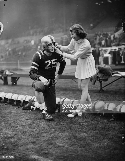 Marcia Carver from Texas adjusts the helmet of AC/2 O J Lindborg of the Burtonwood Rag Bullets in a game of American football The occasion was the...