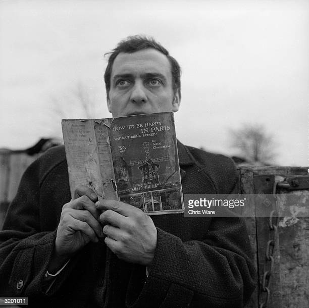 Harry H Corbett looks up from a tattered book called 'How To Be Happy In Paris' in his role as Harold Steptoe a ragandbone man of frustrated...