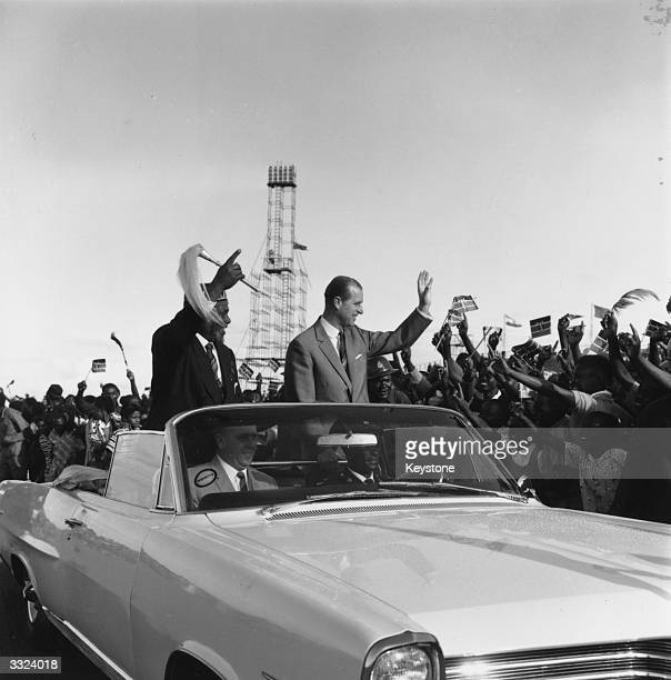 Kenyan Prime Minister Jomo Kenyatta and the Duke of Edinburgh drive through cheering crowds in Nairobi during the Independence celebration