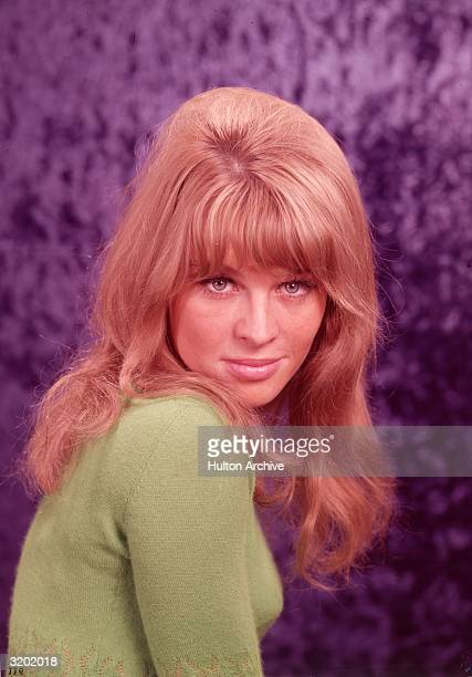 Studio portrait of British actor Julie Christie smiling with her chin on her shoulder against a purple background Christie wears a lime green sweater...