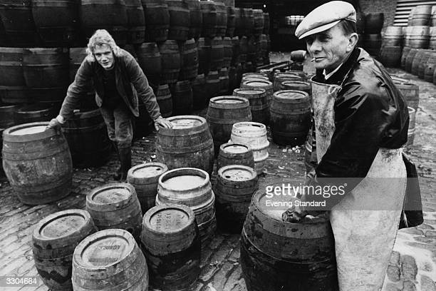 Workers at Young's brewery unbung barrels for filling with beer