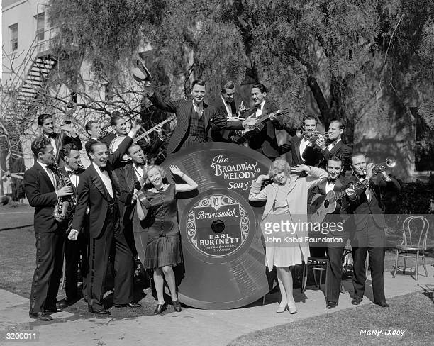 Charles King Anita Page and Bessie Love pose with Earl Burtnett and his Brunswick Orchestra and a huge version of the 'Broadway Melody' song on disc...