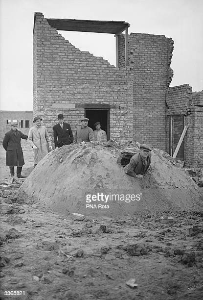 Man climbing out of the emergency exit of a newly designed steel air raid shelter during a demonstration.