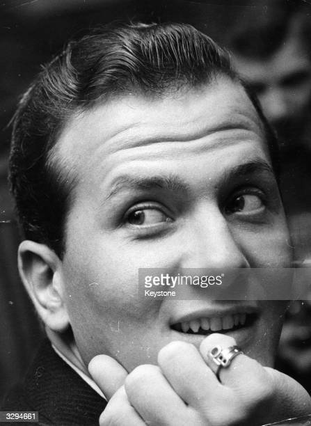 American singer Pat Boone, wearing his PB ring, on his arrival at London Airport; he is to star in the Val Parnell Sunday Night At The Palladium show.