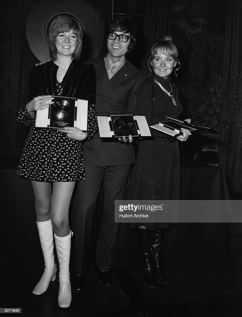 Cilla Black, Cliff Richard and Lulu, holding their awards at the 'Disc and Music Echo' Valentine Awards ceremony at the Cafe Royal in London, 1970, where Cilla wrested the Top British Female Singer award from Lulu, who kept the other three titles she one last year; Top World Female Singer, Miss Valentine and Best Dressed Female Star, while funky Cliff was voted Best Dressed Male Star.