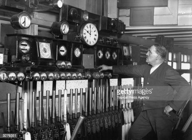 Signalman Roberts of Liverpool Street Station London synchronising the clocks which send the time out to all the signal boxes