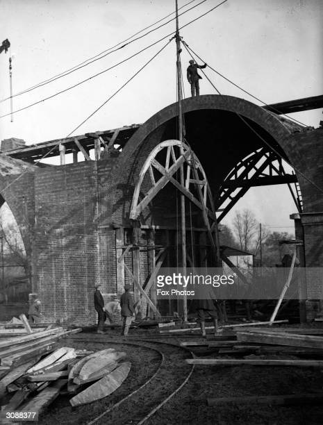 Workmen remove the scaffolding from one of the completed arches of the viaduct beyond Chase Side in Southgate, part of the extension of the...
