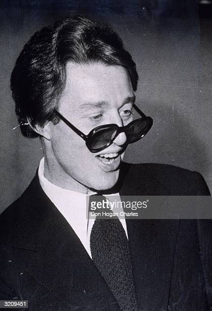 Candid portrait of American fashion designer Halston wearing dark sunglasses pushed down to the tip of his nose, New York City. He designed hats and...