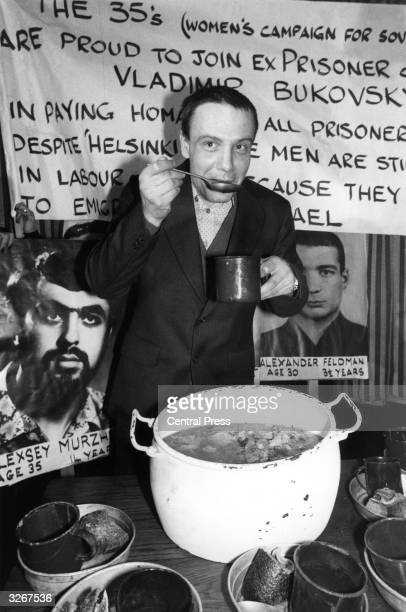 Surrounded by posters of Russian prisoners of conscience Vladimir Bukovsky tastes a symbolic meal which had been prepared to pay homage to those...