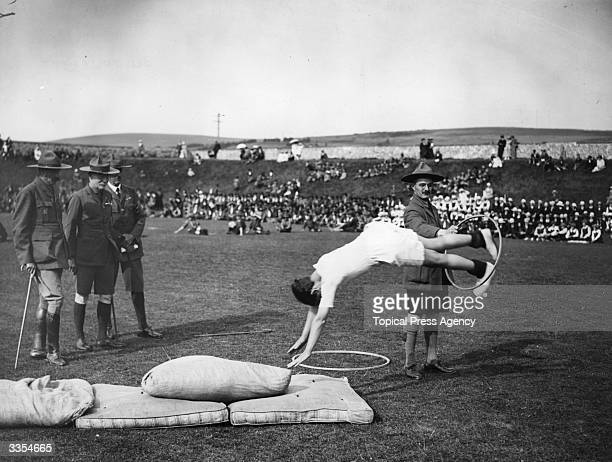 Robert Baden Powell founder of the Scout Movement and Chief Scout takes an interest in a display of tumbling at a Grand Rally of Scouts and Guides at...
