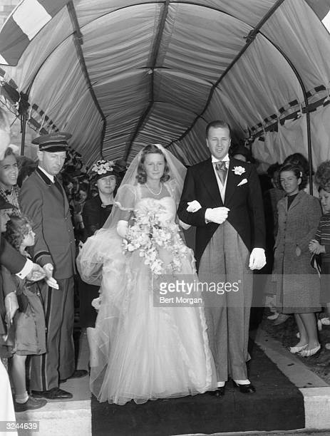 EXCLUSIVE American automobile manufacturing heir Henry Ford II stands arminarm with his new bride Anne McDonnell at the end of an aisle in a tent...