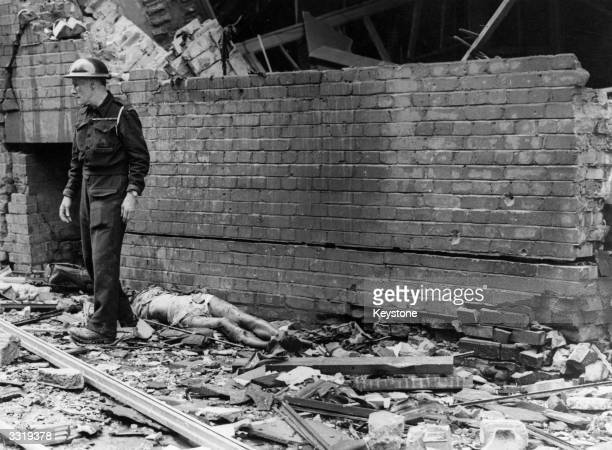 An Air Raid Warden surveys the damage caused by a flying bomb in Aldwych London a corpse lies behind him