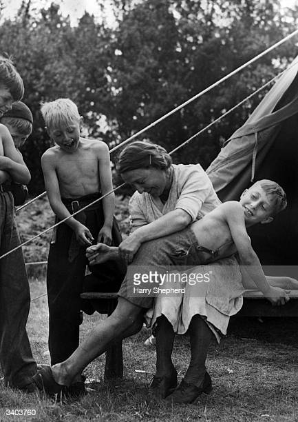 One of a group of boys from Deptford London on a camping trip at Wotton Hatch near Dorking has his trousers mended by Mrs Workman who also does the...