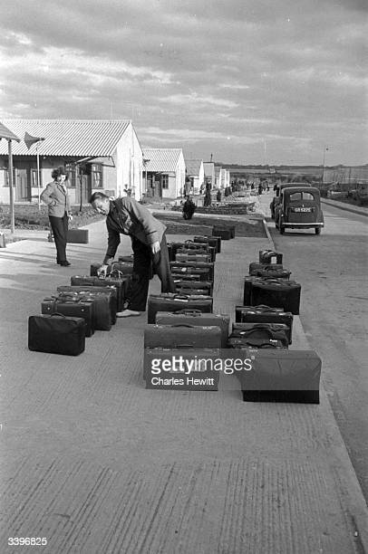 A man examining a row of suitcases in a Butlin's holiday camp Original Publication Picture Post 4136 Life In A Holiday Camp pub 1946