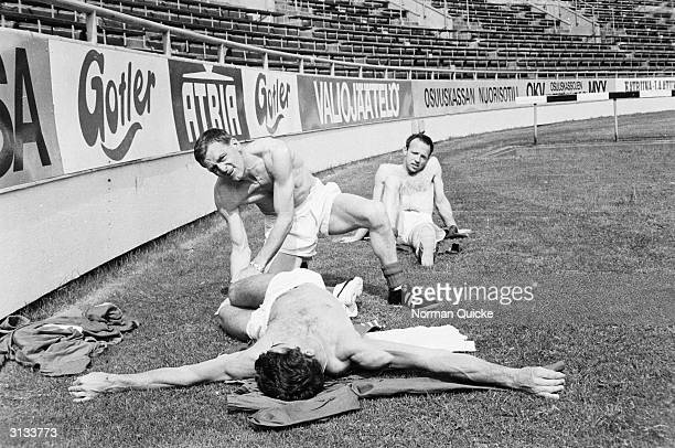 Nobby Stiles watches a trainer help Peter Bonetti perform a few warmup exercises during the England team's preWorld Cup tour