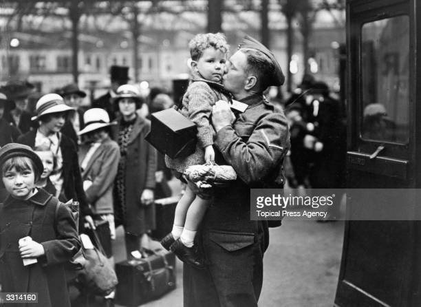 A soldier home on leave from the British Expeditionary Force says goodbye to his baby son at the evacuation point in Greater London