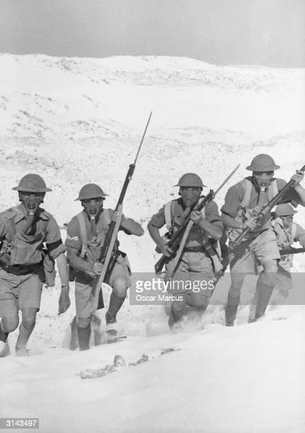 British infantry advancing wearing gas masks during exercises at Mersa Matruh in Egypt