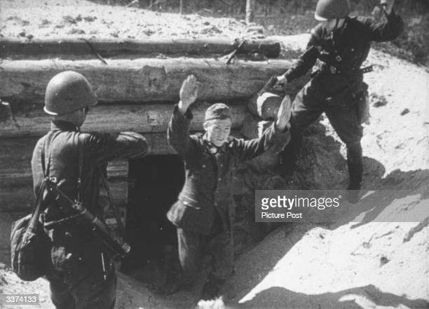 Red Army soldiers aiming their weapons at a German soldier emerging from a captured Nazi dugout who raises his arms in surrender. Original...