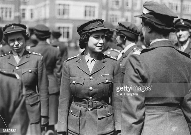 Queen Elizabeth II attending the passing out parade of the ATS whilst wearing full military uniform.