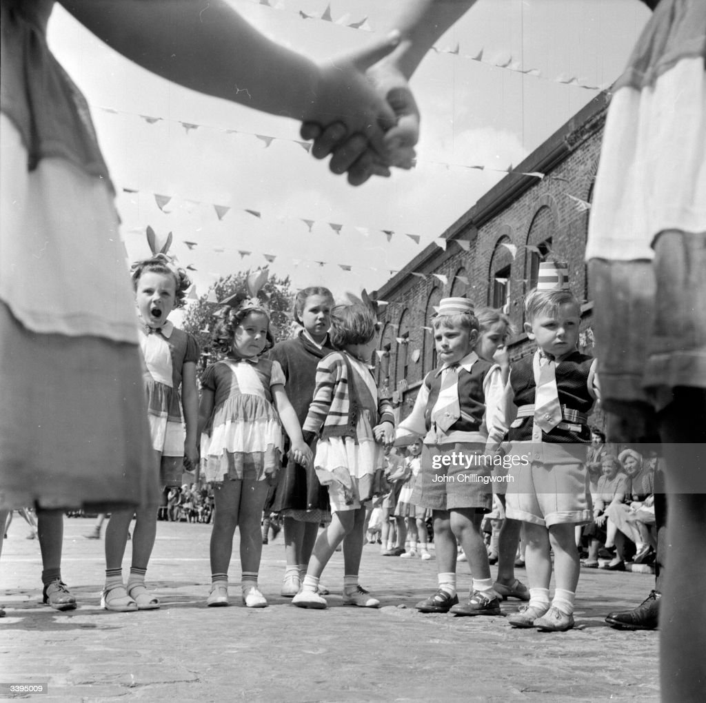 Children playing party games at a street party at Morpeth Street, in London's East End, to celebrate the coronation of Queen Elizabeth II. Original Publication: Picture Post - 6542 - Cockneys' Own Party - pub. 1953
