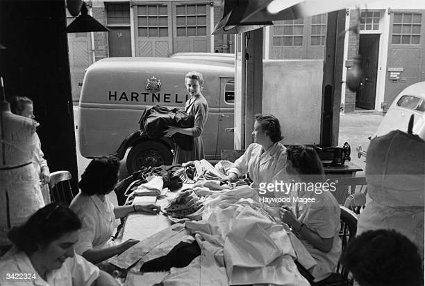 Women working in Norman Hartnell's salon watch as the Queen's coronation dress is taken for delivery to Buckingham Palace. Original Publication:...