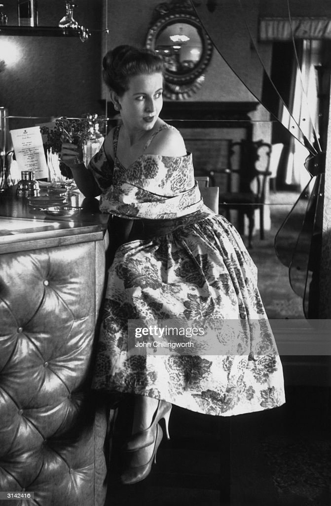 Picture Post girl Ann West wearing a cocktail dress designed by Alice Edwards. Ann will be wearing the dress in Eastbourne and there will be cash prizes for any Picture Post reader who spots Ann and approaches her with a copy of the magazine. Original Publication: Picture Post - 8543 - Hunt These Picture Post Girls - pub. 1956