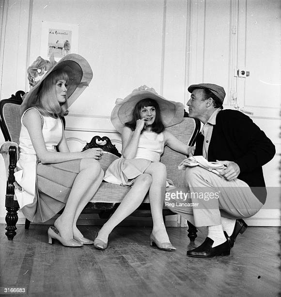 American film star Gene Kelly talking to French film actress Catherine Deneuve and her older sister Francoise Dorleac on location for the filming of...