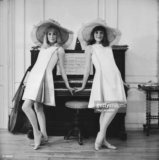 Film actress Catherine Deneuve and her older sister Francoise Dorleac posing against a piano on location for the film 'Les Demoiselles de Rochefort'...