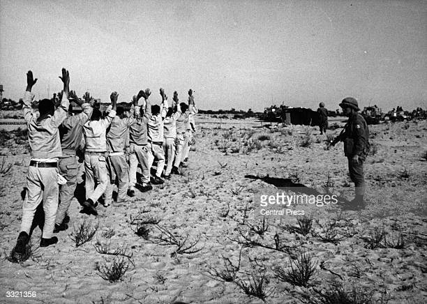 Egyptian prisoners of war holding their hands aloft after being rounded up by Israeli forces in the Sinai desert following the SixDay War