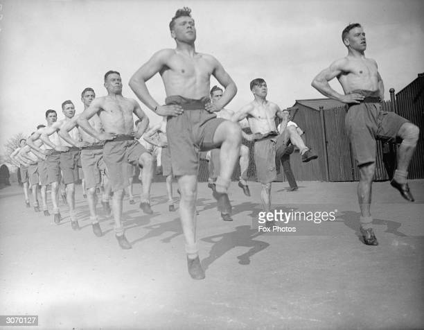 Stripped to the waist, would be soldiers get down to some physical training at an army vocational training camp, Aldershot, Hampshire.