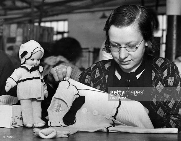 Worker finishing off a woollen suit at the Windsor factory at Blackpool. The Duchess of York ordered the clothing worn by the woolly Windsor doll for...