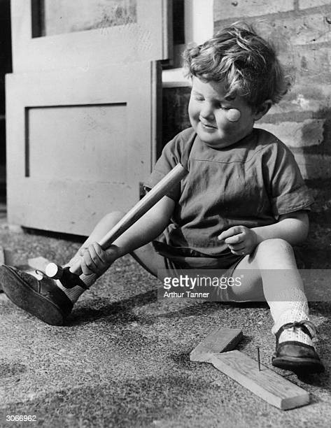 A little boy examines a hammer a nursery school in Kintore Way Bermondsey London The predominant feature of the school is to teach deprived children...
