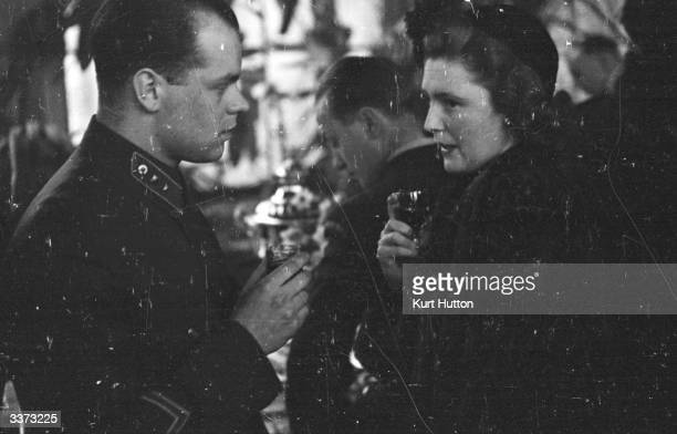 Mrs Pamela Churchill wife of English journalist Randolph Churchill talking to a Soviet soldier at the Soviet Embassy in London during celebrations...