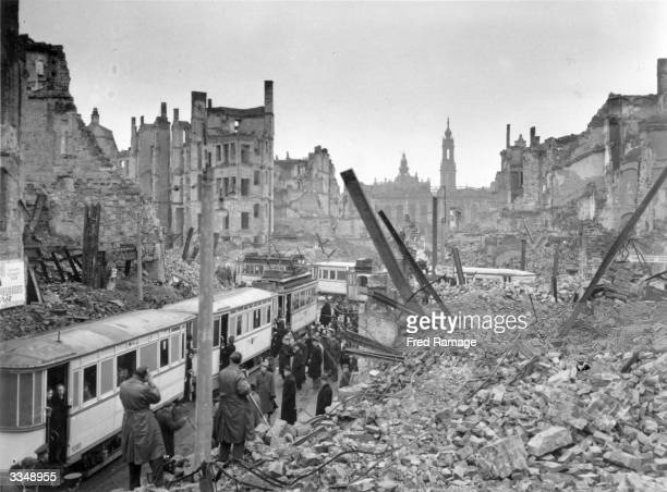 People getting on trams in the midst of the ruins left by an Allied air raid on Johannstrasse Dresden in the Soviet zone of Germany after the Second...