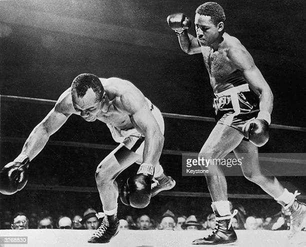 American boxer Ezzard Charles stands over Jersey Joe Walcott of the USA as he falls during their world heavyweight title fight in Detroit Charles won...